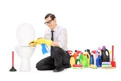Человек сидя туалетом с чистящими средствами Стоковые Фото