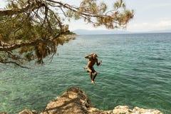Человек скача внутри к морю стоковая фотография