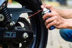Человек смазывая цепь мотоцикла Стоковая Фотография