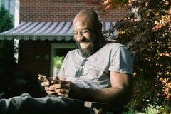 Человек смеется над текстовым сообщением чтения в саде Стоковые Фотографии RF