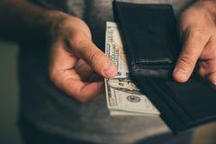 Человек смотрит в бумажнике cash Богатый человек подсчитывая его деньги конец вверх стоковая фотография rf