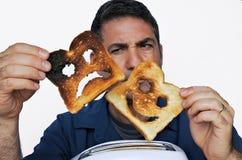 Человек смотрит 2 различных куска хлеба здравицы Стоковые Изображения RF