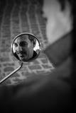 Человек смотря в зеркале самоката Стоковая Фотография RF