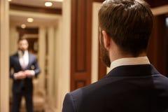 Человек смотря в костюме зеркала нося Стоковые Фото