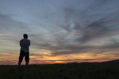Человек смотря заход солнца Стоковые Изображения