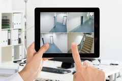 Человек смотря дома видео CCTV камеры Стоковые Изображения