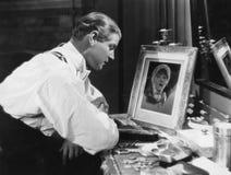 Человек смотря портрет женщины (все показанные люди более длинные живущие и никакое имущество не существует Гарантии поставщика к стоковое фото rf