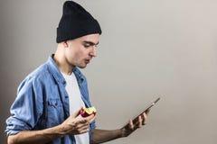 Человек смотря удивленный на ПК таблетки Стоковое Фото