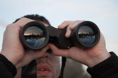 Человек смотря через бинокли на заходе солнца Стоковое Изображение RF