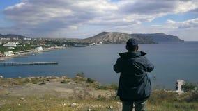 Человек смотря через бинокли на заливе акции видеоматериалы