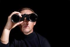 Человек смотря через бинокли на темной предпосылке стоковые фото