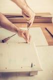 Человек собирает шкаф мебели, переплетает винты в шлицах, собрание мебели стоковое фото rf