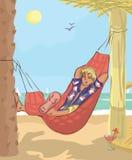 Человек спать в гамаке на пляже Стоковые Изображения