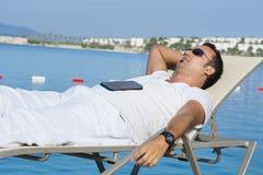 Человек спать на пляже Стоковые Фото