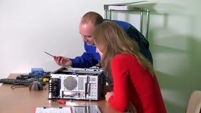 Человек специалисту по ИТ ремонтируя ее компьютер коллеги в офисе видеоматериал