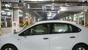 Человек спешит на встрече Получает в автомобиль и выходит подземная автостоянка Видео содержит звук сток-видео