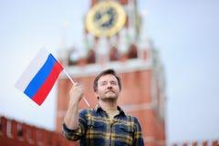 Человек среднего возраста с русским флагом с башней Россией Spasskaya, Москвой на предпосылке Стоковое фото RF