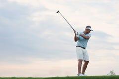 человек Средний-взрослого играя гольф против неба стоковая фотография rf