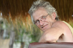 Человек старшия зрелый & ослабленный зрелищами усмехаться стоковое фото