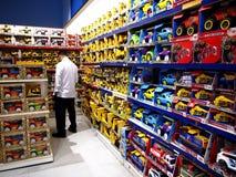 Человек стоит в середине полок с автомобилями игрушки в магазине игрушек Стоковые Фотографии RF