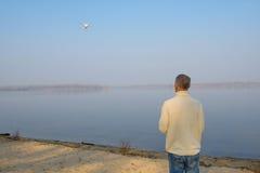 Человек стоит на речном береге и контролирует трутня Стоковое фото RF