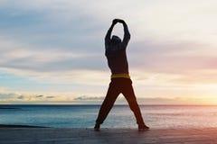 Человек стоит смотрящ на море восхищая заход солнца и делая тренировки Стоковое Изображение