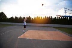 Человек, стоящ высокорослый, подготавливая снять баскетбол, в парке Стоковые Фото