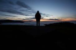 Человек стоя в заходе солнца над долиной Стоковое Изображение RF