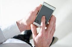 Человек стоя используя smartphone стоковая фотография rf