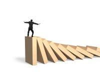 Человек стоя и балансируя на домино Стоковое фото RF