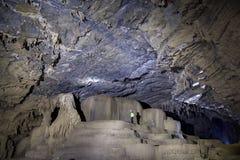 Человек стоя на группе в составе пещера 3 сталактита Стоковые Изображения RF