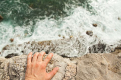 Человек стоя на краю скалы стоковое изображение