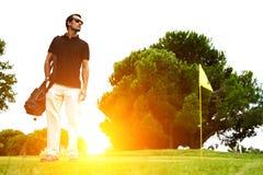Человек стоя на поле для гольфа на заходе солнца Стоковые Изображения