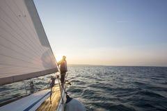 Человек стоя на фронте роскошной яхты в море стоковая фотография rf