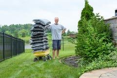 Человек стоя около фуры с положенным в мешки mulch Стоковая Фотография