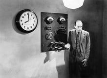 Человек стоя рядом с электрическим переключателем (все показанные люди более длинные живущие и никакое имущество не существует Га стоковое фото rf