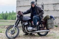 Человек столба апоралипсический на мотоцикле около разрушенного здания Стоковая Фотография RF