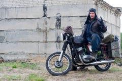 Человек столба апоралипсический на мотоцикле около разрушенного здания Стоковое Изображение