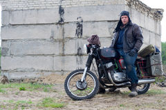 Человек столба апоралипсический на мотоцикле около разрушенного здания Стоковая Фотография