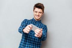Человек сфокусированный на игре на smartphone стоковая фотография rf