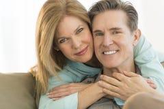 Человек счастливой женщины обнимая на софе дома Стоковые Фото