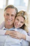 Человек счастливой женщины обнимая от заднего дома Стоковая Фотография