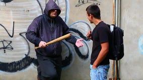 Человек с бейсбольной битой против подростка сток-видео
