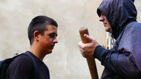 Человек с бейсбольной битой против подростка видеоматериал