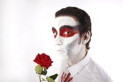 Человек с белой тушью и кровопролитной рубашкой держит красную розу Стоковое Фото