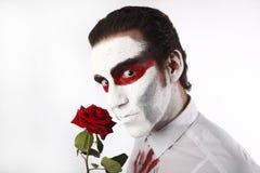 Человек с белой тушью и кровопролитной рубашкой держит красную розу стоковое изображение