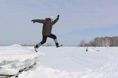 Человек с бородой в серой крышке скача от блока льда Стоковая Фотография