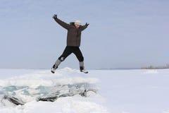 Человек с бородой в серой крышке скача от блока льда Стоковое Фото