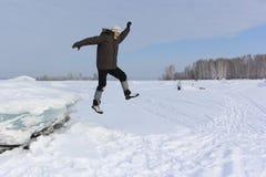 Человек с бородой в серой крышке скача от блока льда Стоковая Фотография RF