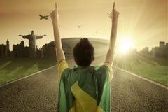 Человек с бразильским флагом поднимает его руки Стоковая Фотография